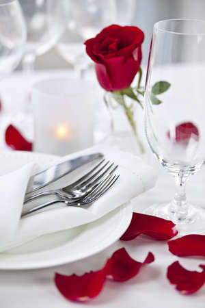 Romantic table setting with rose petals plates and cutlery Archivio Fotografico