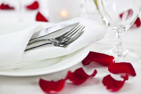 Romantic table setting with rose petals plates and cutlery Stock Photo