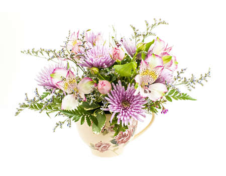 Bouquet of colorful flowers arranged in small vase isolated on white background photo