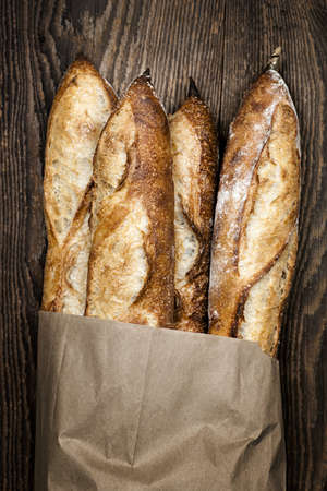 artisan: Four baguette bread loaves in paper bag on wooden background