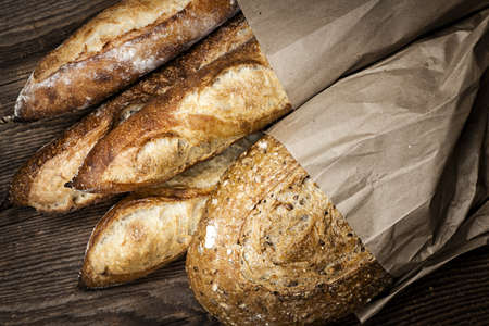 artisan bakery: Fresh baked rustic bread loaves in paper bags on dark wood background Stock Photo
