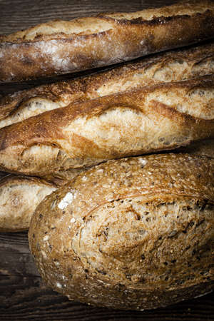Fresh baked rustic bread loaves on dark wood background photo