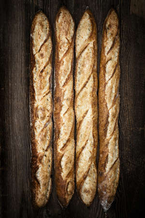 Four whole baguette bread loaves on dark wooden background Stock Photo - 17664313