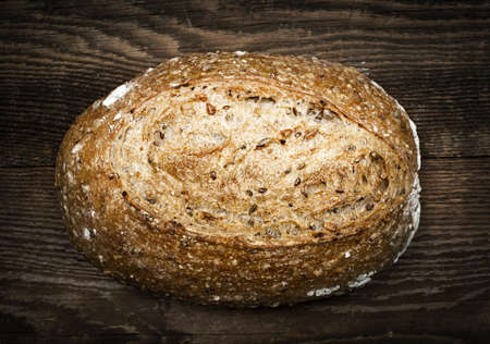 Artisan loaf of freshly baked multigrain bread on wooden background Stock Photo - 17664303