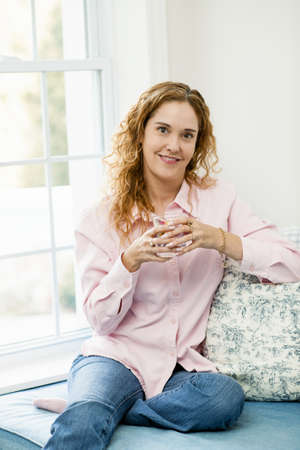 Smiling caucasian woman relaxing by window with glass of water Stock Photo - 17592204