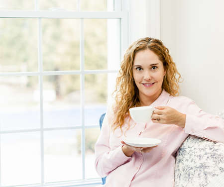 Smiling caucasian woman relaxing by window holding cup of coffee Stock Photo - 17592205