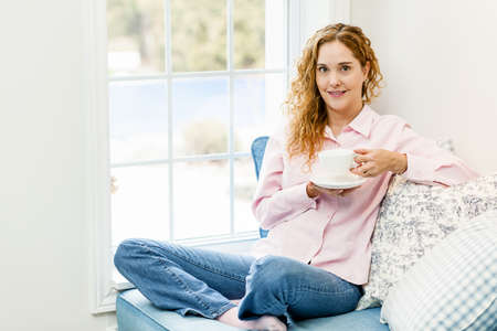 Smiling caucasian woman relaxing by window holding cup of coffee Stock Photo - 17592194