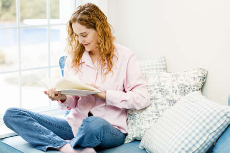 Smiling caucasian woman reading book by window at home Stock Photo - 17592197