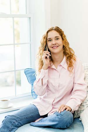 cordless: Smiling caucasian woman talking on cordless telephone at home Stock Photo