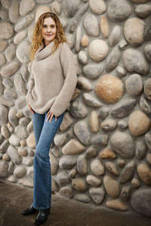 Smiling woman standing in front of stone wall bull body Stock Photo - 17592190