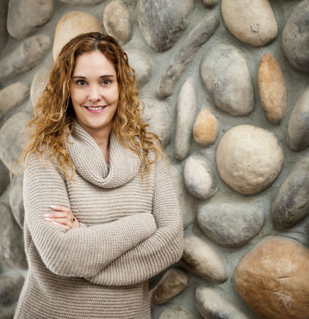 Smiling woman standing in front of stone wall Stock Photo - 17592200