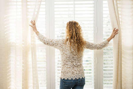 a blind: Woman looking out big bright window with curtains and blinds Stock Photo
