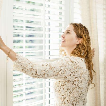 big windows: Счастливая женщина, глядя в большое яркое окно с занавесками и жалюзи