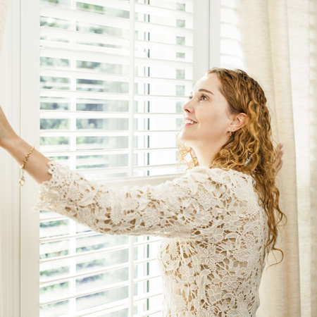 window treatments: Happy woman looking out big bright window with curtains and blinds