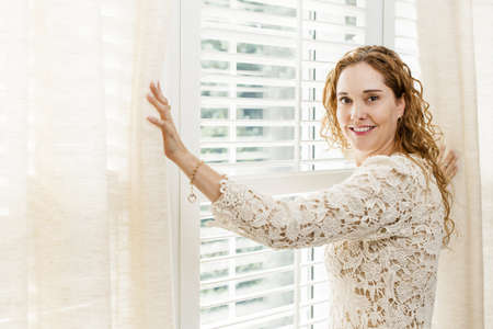 a blind: Happy woman opening curtains on big sunny window with shutters