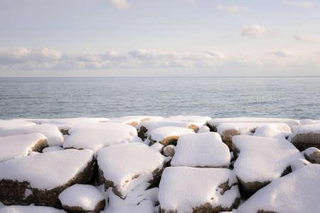 understated: Rocks under snow on winter shore of lake Ontario in Sylvan park Toronto