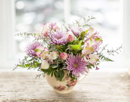 teacup: Bouquet of colorful flowers arranged in small vase