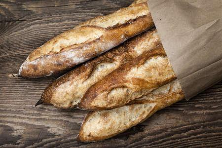 pan frances: Cuatro panes de baguette de pan en una bolsa de papel sobre fondo de madera