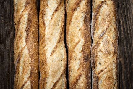 Baguette bread loaves in a row on wooden background photo
