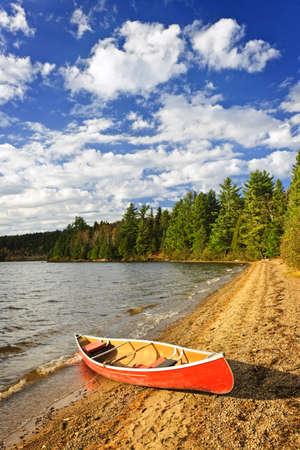 fiberglass: Canoa roja en la playa en el Lago de Dos Ríos, Ontario, Canadá Foto de archivo