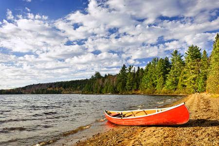 canoa: Canoa roja en la playa en el Lago de Dos Ríos, Ontario, Canadá Foto de archivo