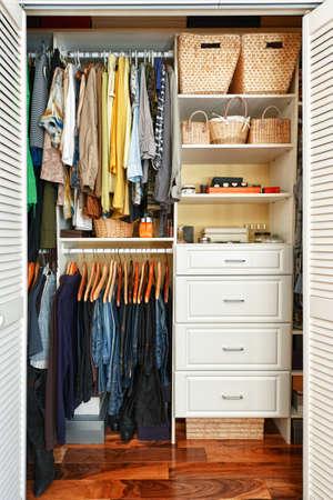 ropa colgada: Ropa colgada en el armario pulcramente organizada en casa Foto de archivo