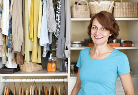 clothes organizer: Happy woman standing in front of custom organized closet at home