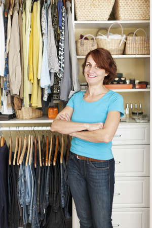 organizing: Happy woman standing in front of custom organized closet at home