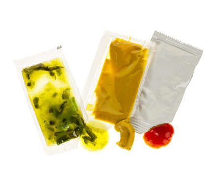 packets: Relish mustard and ketchup condiment packets open on white background