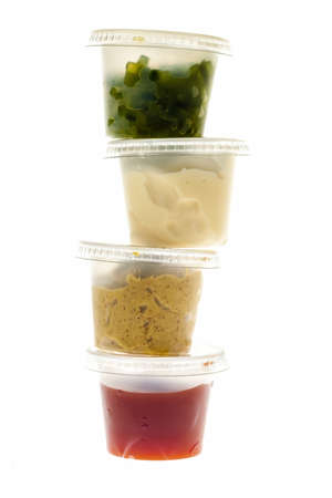 Relish mustard ketchup and mayonnaise condiments in clear containers stacked on white background Stock Photo