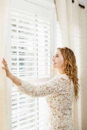 cortinas blancas: Mujer feliz mirando por la ventana brillante grande con cortinas y persianas