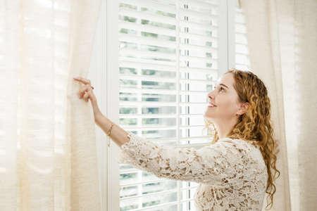cortinas: Mujer feliz mirando por la ventana brillante grande con cortinas y persianas