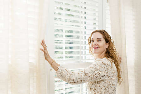 Happy woman opening curtains on big sunny window with shutters photo