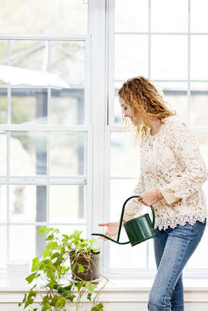 Smiling woman watering green plant at home by window