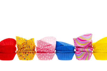 Several stacks of colorful muffin or cupcake cups isolated on white background as border photo