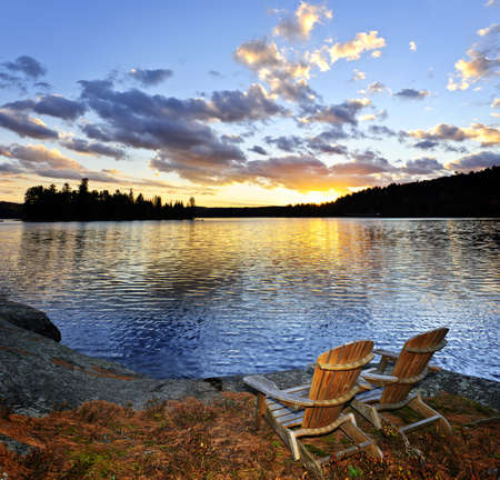 adirondack chair: Wooden chair on beach of relaxing lake at sunset in Algonquin Park, Canada