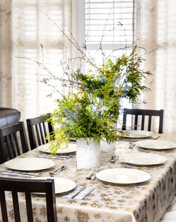 Dining table decorated for Christmas with eight place settings and evergreen centerpiece Stock Photo - 18341725