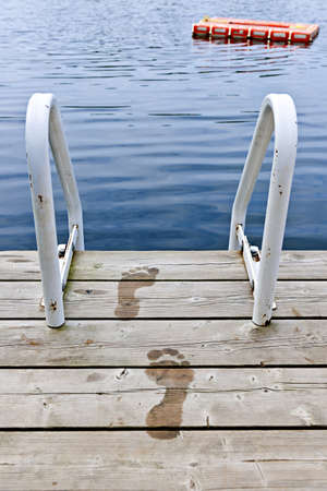 Wet footprints on dock with ladder and diving platform at calm summer lake in Ontario Canada Stock Photo - 18341666