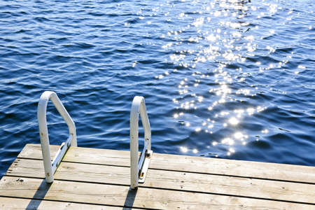 Dock and ladder on calm summer lake with sparkling water in Ontario Canada Stock Photo - 18341720