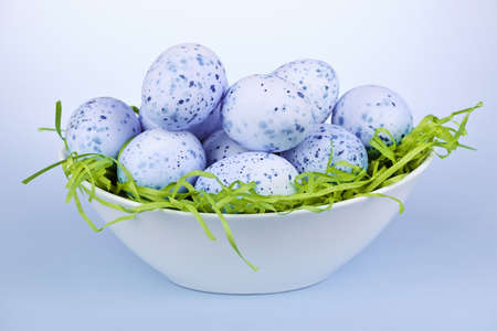 Many blue speckled easter eggs in bowl on green paper grass Stock Photo - 18341679