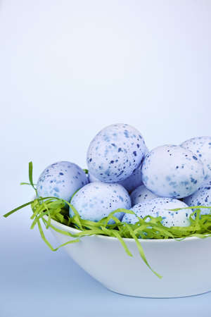 Many blue speckled easter eggs in bowl on green paper grass with copy space Stock Photo - 18341648