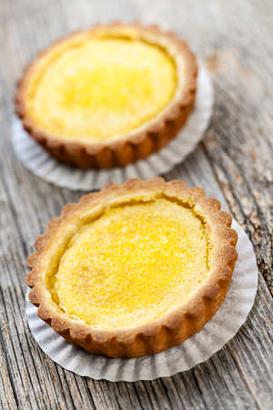 Two gourmet fresh lemon dessert tarts on wooden background Stock Photo - 18341780