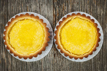 Two fresh gourmet lemon dessert tarts on wood background from above Stock Photo - 18341814