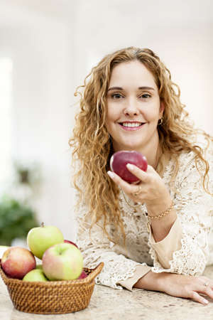 Portrait of smiling woman holding red apple leaning on countertop in kitchen at home Stock Photo - 18341643