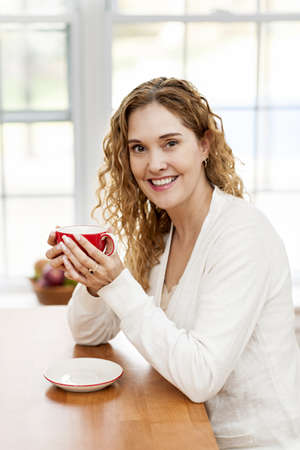 Portrait of smiling woman holding red coffee cup sitting at table in home kitchen by window photo