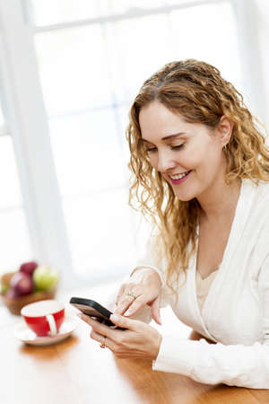 Portrait of smiling woman holding cell phone sitting at table in home kitchen by window Stock Photo - 18341649