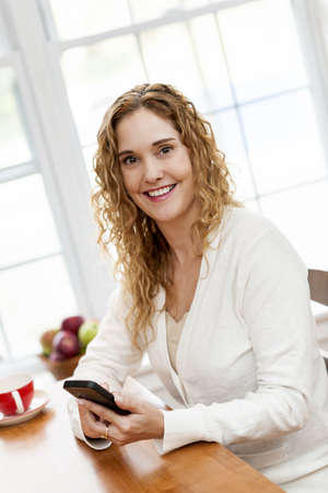 Portrait of smiling woman holding cell phone sitting at table in home kitchen by window Stock Photo - 18341592