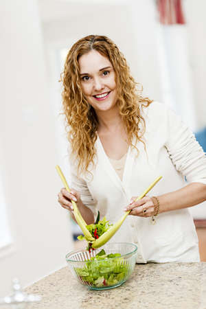 Portrait of happy woman mixing salad in kitchen at home Stock Photo - 18341672