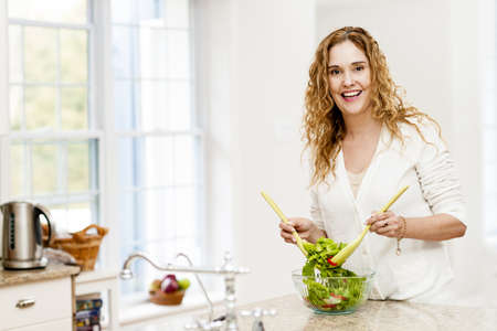 salad greens: Portrait of happy woman mixing salad in kitchen at home Stock Photo