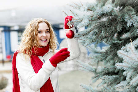 Joyful woman hanging Christmas ornaments on spruce tree outdoors in yard near home Stock Photo - 18341737